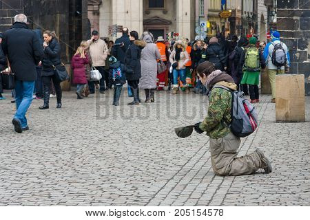 PRAGUE CZECH REPUBLIC - FEBRUARY 02 2014: Beggar on Charles Bridge. The Charles Bridge is a famous historic bridge that crosses the Vltava river in Prague.