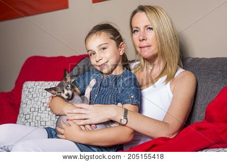 A Little girl with mother and cat on sofe at home