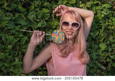 Beautiful young girl with light pink hair and glasses holds a candy caramel in the form of a spiral on a background of green leaves