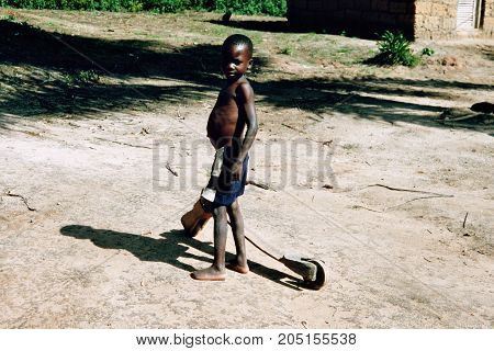 MANGUE, ANGOLA - May 15, 2007: A little boy with his toy scooter.