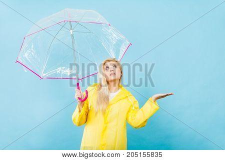 Woman Wearing Raincoat Holding Umbrella Checking Weather