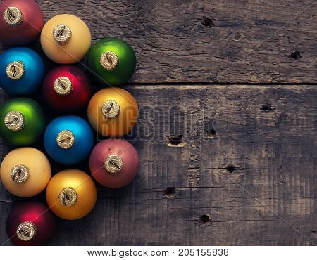 Colorful vintage Christmas baubles on a rustic wooden table with space for text