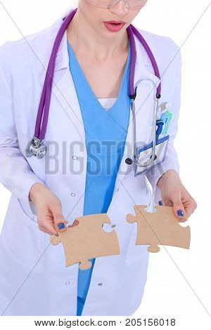 Woman doctor holding two connecting puzzle pieces.