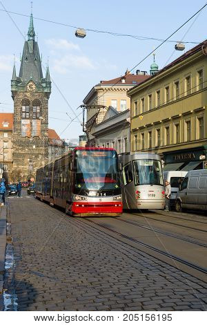PRAGUE CZECH REPUBLIC - FEBRUARY 03 2014: Prague tram on the street. In the background the church bell Holy Roman Emperor Saint Henry II and Saint Cunigunde of Luxembourg