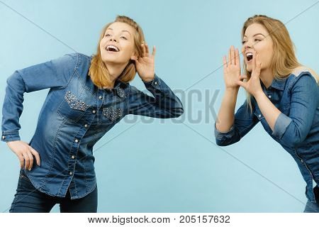 Two women talking gossip telling tales girls talk having fun wearing jeans outfit.