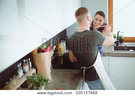 Couple cooking together in their kitchen at home.