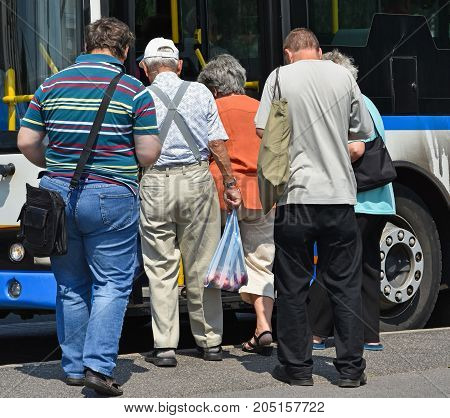 People getting in to the bus at the bus stop