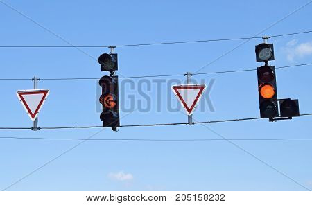Street lights and yield road signs against sky