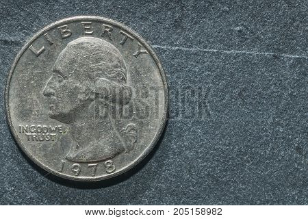 A quarter dollar coin on a grey background