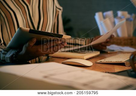 Documents and digital tablet in hands of business lady