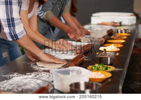 Hands of people making pizzas together in cafe kitchen