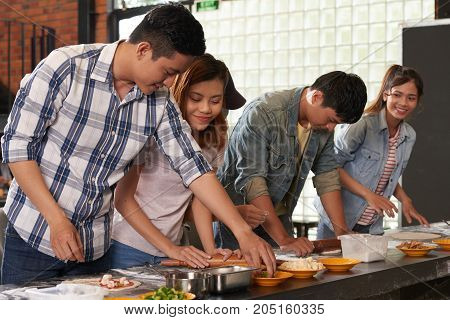 Young couple making pizza at culinary workshop