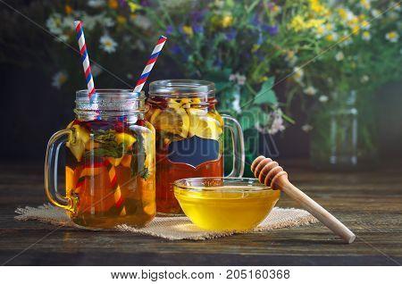 Fresh honey, field flowers, lemon tea and fruit on a wooden table. Selective focus. Still life.