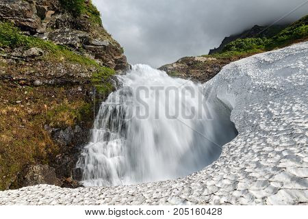 Amazing summer mountain landscape of Kamchatka Peninsula: beautiful view of tranquil waterfall falling into the snowfield in Mountain Range Vachkazhets. Kamchatka Region Russian Far East Eurasia.