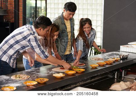 Vietnamese young people making pizza at workshop