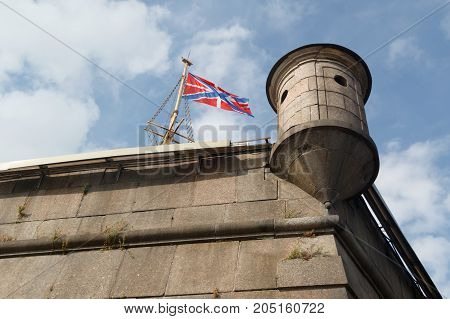 Flag and turret on Naryshkin bastion of Peter and Paul Fortress on a background cloudy sky in St-Petersburg, Russia