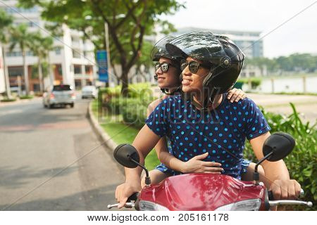 Smiling couple on scooter in helmets and sunglasses