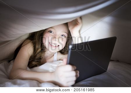 A Cute little girl alone with tablet computer under blanket at night in a dark room