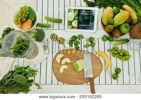 Tablet computer, cut fruits and greens on table, view from above