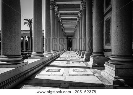 Rome, Italy - August 21, 2016: Outdoors view of Colonnade in the Papal Basilica of St. Paul outside the Walls . It is one of Rome's four major basilicas. Black and white image