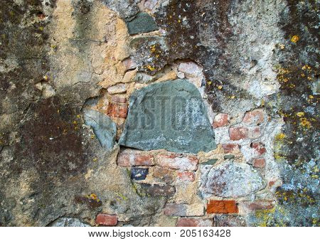 Wall With Plaster Cracked And Worn By Time And Neglect