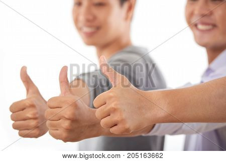 Group of smiling young people showing thumbs-up