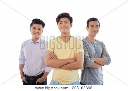 Three confident young men smiling and looking at camera