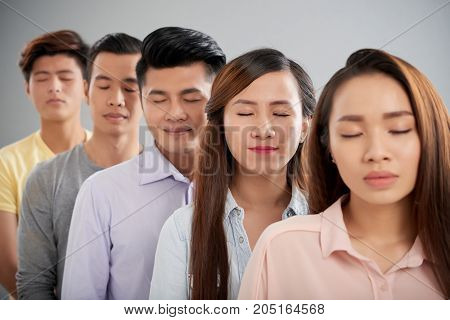 Young Asian people closing their eyes to make a wish