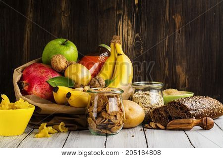 Assortment of products rich of complex carbohydrates. Healthy food on wooden background. Space for text