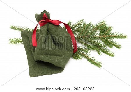 Christmas present bag with red ribbon bow laying in fir tree braches isolated on white background. Christmas decoration.