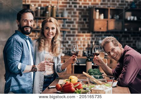 Friends Drinking Wine While Cooking Dinner