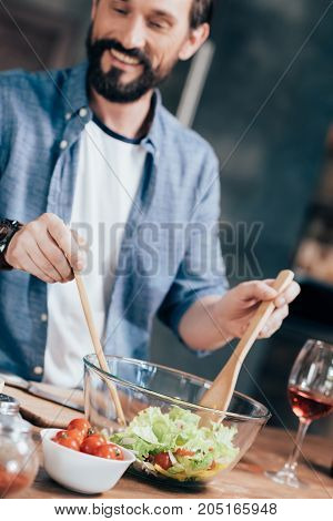 smiling bearded man preparing vegetable salad at home