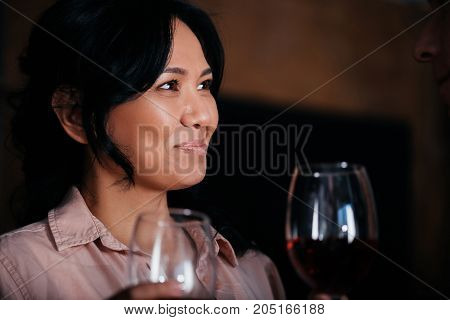 beautiful mature asian woman drinking wine and looking away