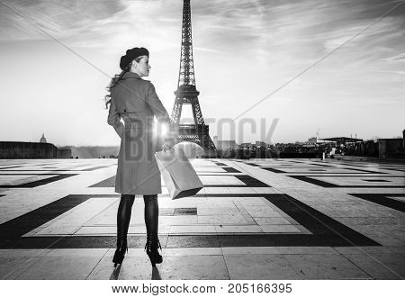 Bright in Paris. Seen from behind trendy tourist woman in red coat in Paris France with shopping bag looking aside