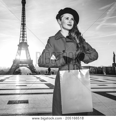 Bright in Paris. smiling modern traveller woman in red coat in the front of Eiffel tower in Paris France with shopping bag looking into the distance