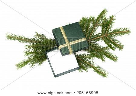 Christmas present box laying in fir tree branches isolated on white background. Christmas decoration.