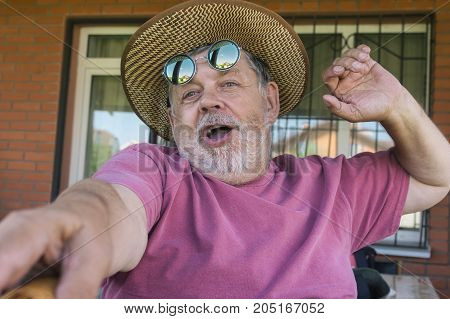 Portrait of bearded singing senior man making selfie with pleasure
