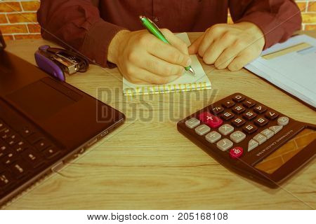 Businessman at a desk in an office typing on a laptop computer and Calculator. Cheerful young businessman sitting at the table with laptop and stretching in the office - Retro color