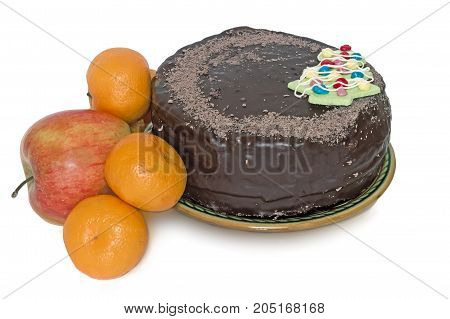 A big chocolate cake with decoration in the form of a Christmas tree on a ceramic dish and fruit. Presented on a white background.