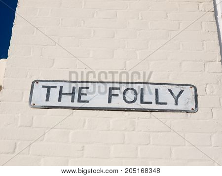 street sign name the folly white and black on wall; England; Essex
