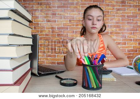 Student Young Girl working on his homework. Girl with lots of books studying for exams. Education and school concept