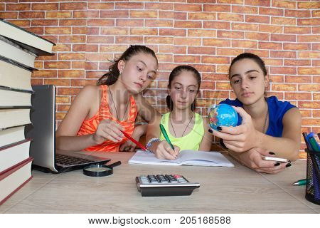 Students Three Young Girls working on his homework. Three Girls with lots of books studying for exams. Thoughts education creativity concept