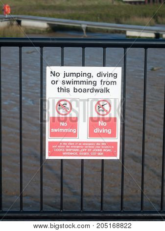no jumping diving or swimming from this boardwalk sign on railings at dock; England; Essex