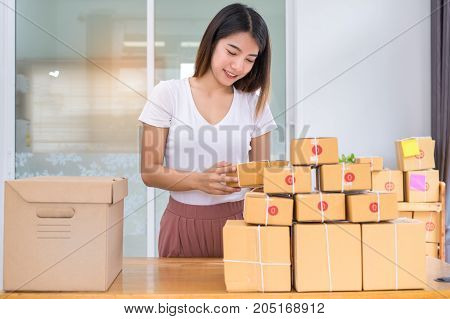 Young asian woman freelancer business small owner working at home office with packaging sort box delivery online market on purchase orders to customer.
