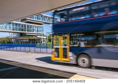 Blurred moving bus at park and ride transport station busway on North Shore New Zealand NZ