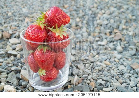 Glass full of red ripe strawberries stands on the grey crushed stones.