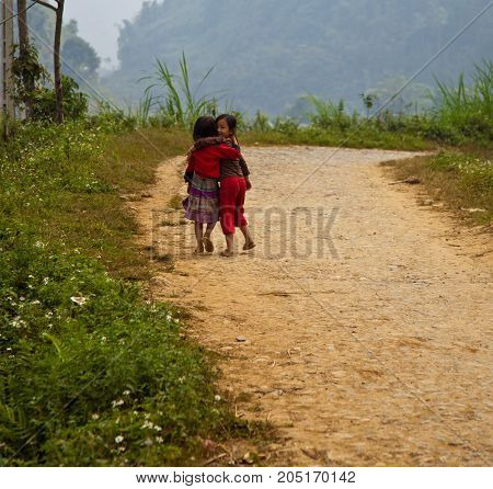 Children Walk Together While One Peeks Back In Sapa, Vietnam
