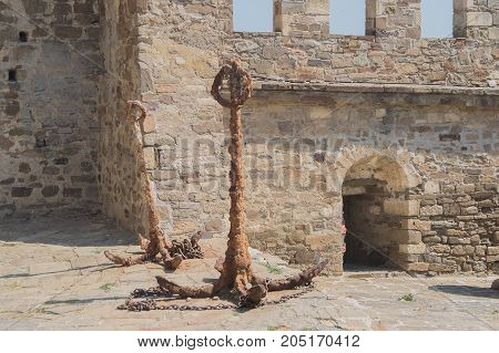 Old ancient metal anchor near old wall of fortress