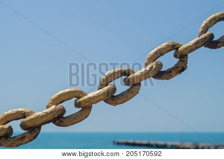 Old metal gold chain on the beach background in the sunlight