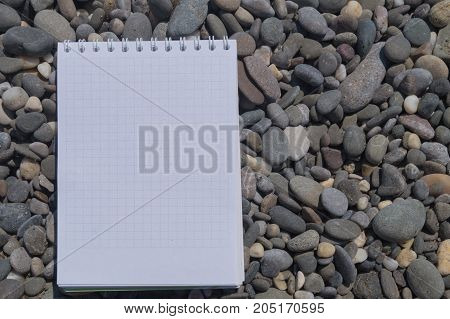 Open white note book on rings on the pebble beach